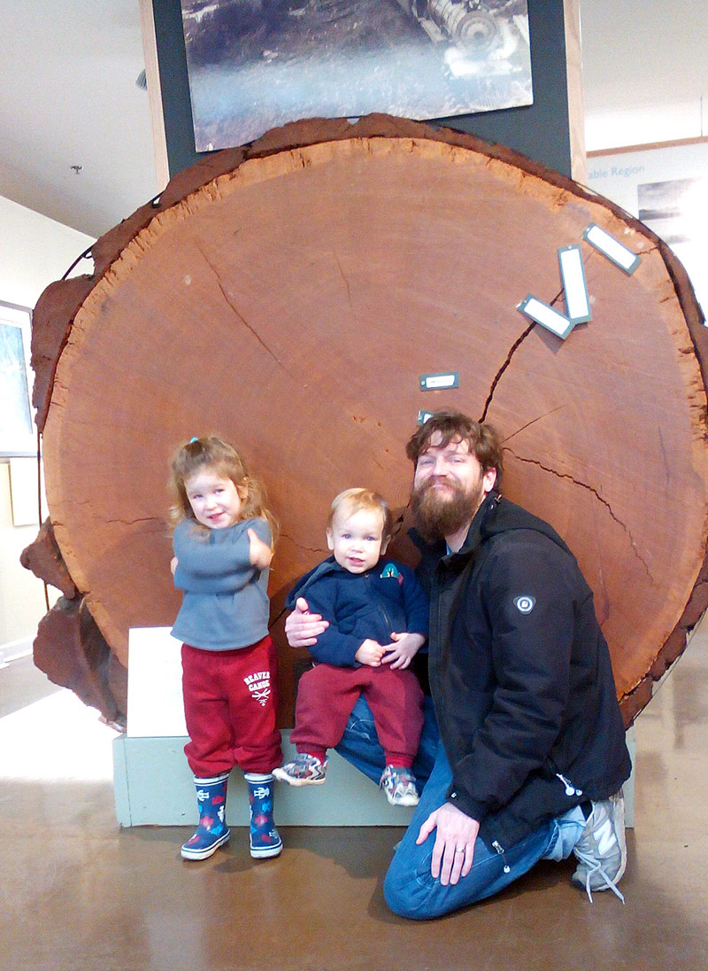 young family with large old growth tree at the Courtenay and District Museum and Palaeontology Centre